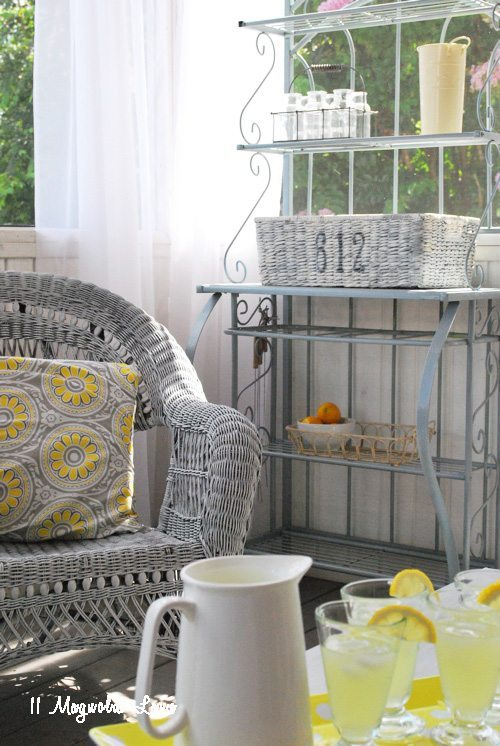 Grey painted baker's rack is repurposed as entertainment center on a screened porch | 11 Magnolia Lane