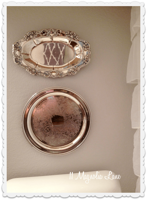 silver platters hung on bathroom wall