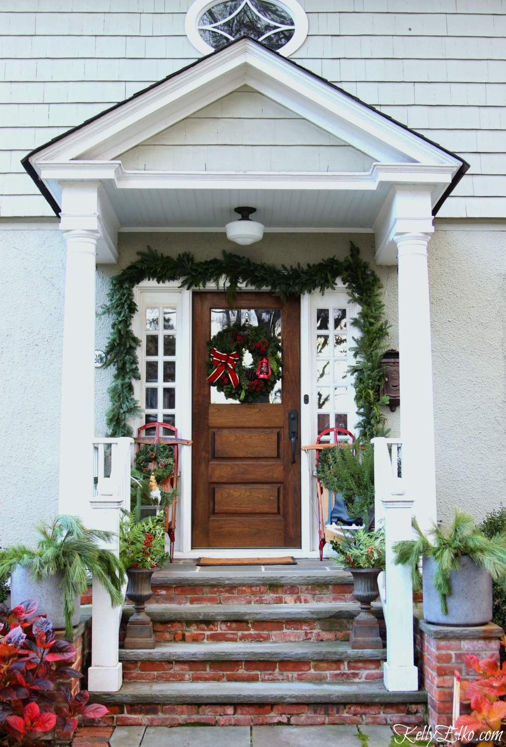 christmas-porch-vintage-sleds-garland-planters