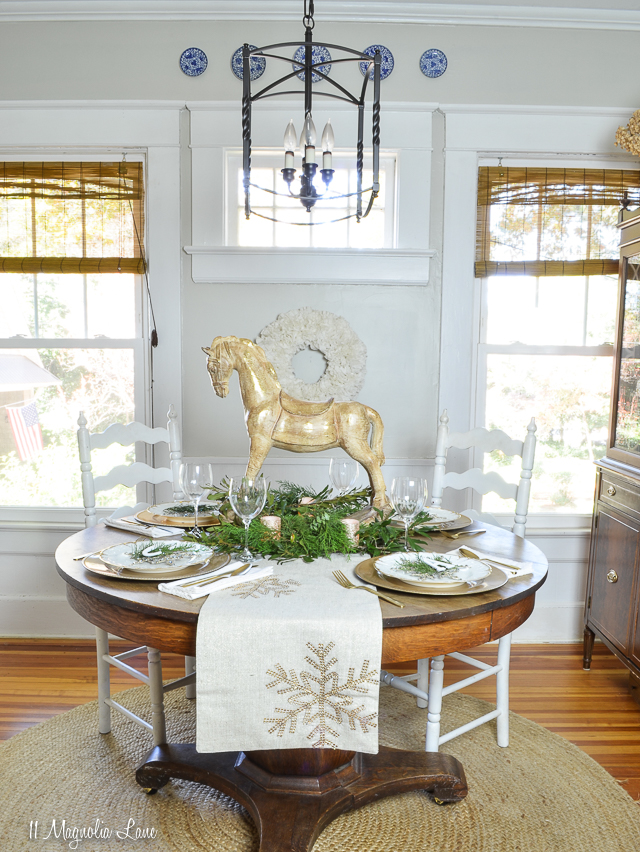 Holiday table with gold, white, evergreen, snowflakes, and rocking horse | 11 Magnolia Lane