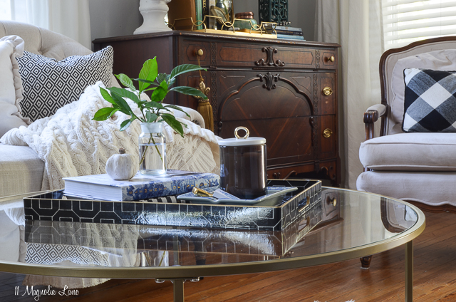 Living room with black and white striped chairs, round gold coffee table, and vintage touches   11 Magnolia Lane