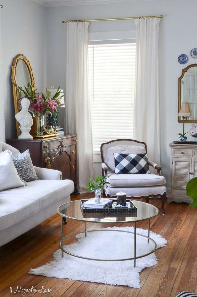 Living room with black and white striped chairs, round gold coffee table, and vintage touches | 11 Magnolia Lane